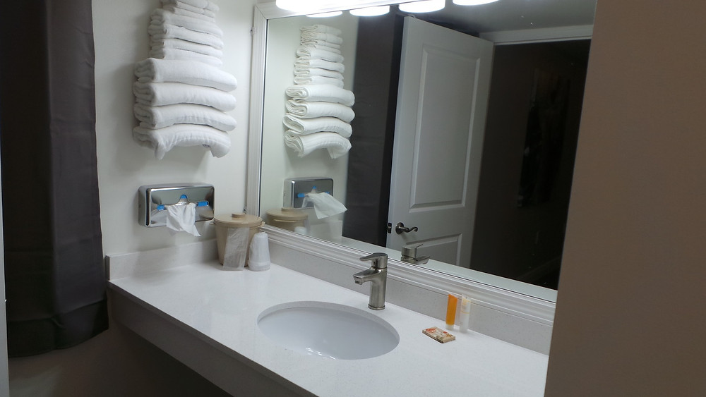 Vanity with sink, tissue holder, towel rack, shampoo, conditioner, light bar, ice bucket