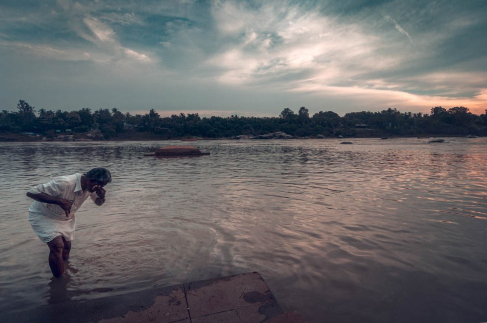 A man offering prayers in the Tungabhadra river Hampi.
