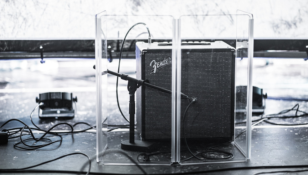A guitar amp being miked up with a Shure SM57 microphone