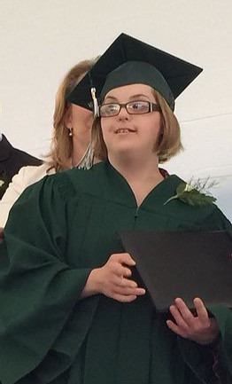 Image of Stephanie Cerep, wearing her green graduation cap and gown, smiling as she holds her diploma.