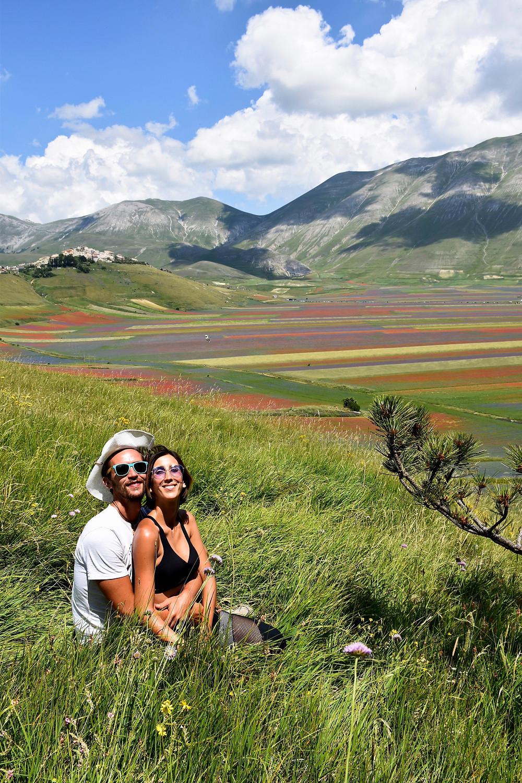 Eugenia e Nicola abbracciati, seduti sul prato verde, e alle nostre spalle la colorata fioritura di Pian Grande e Castelluccio di Norcia, Umbria.