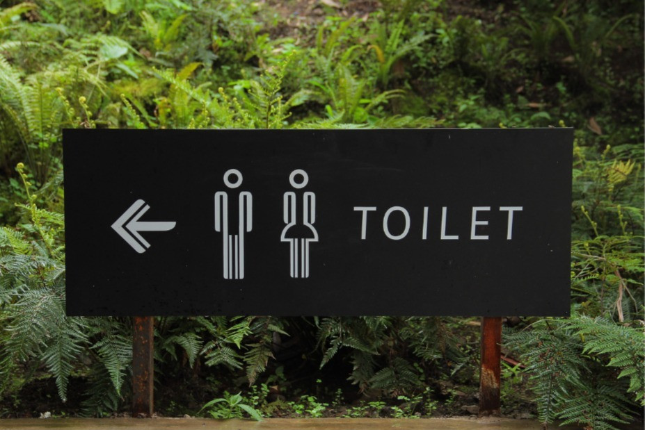 A sign outside pointing to the location of the toilet for men and women