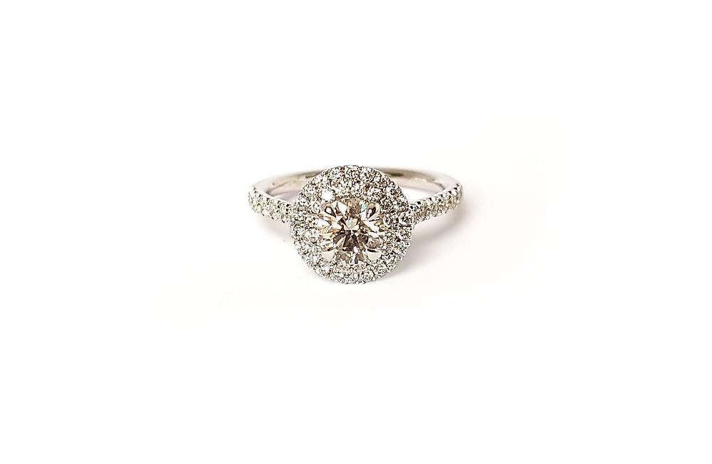 Elegants baltā zelta gredzens ar halo stilā izkārtotiem briljantiem.