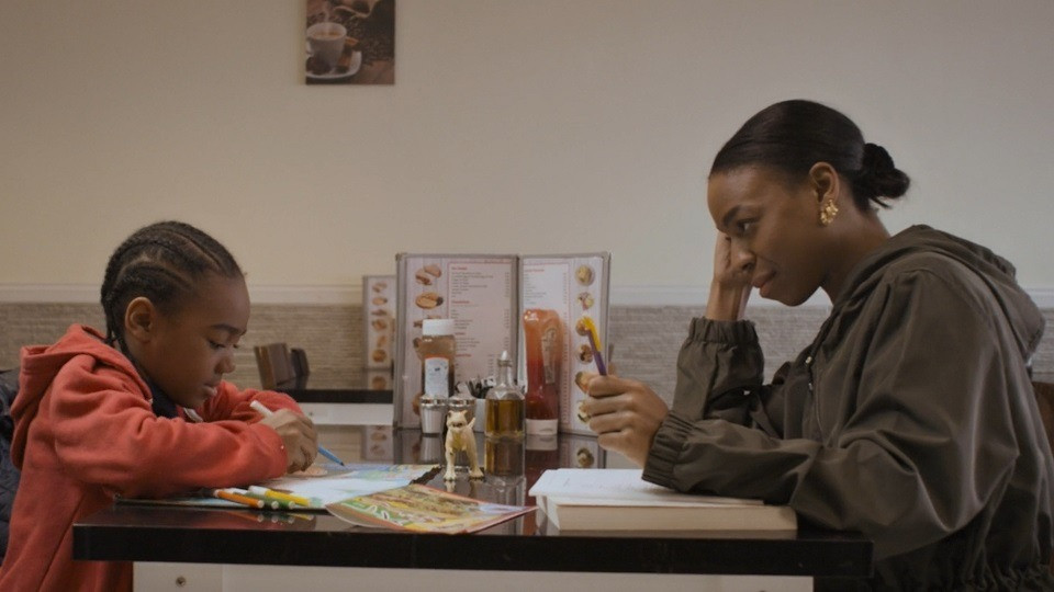 A film still from the movie REAL. Showing a woman and child eating inside a diner.