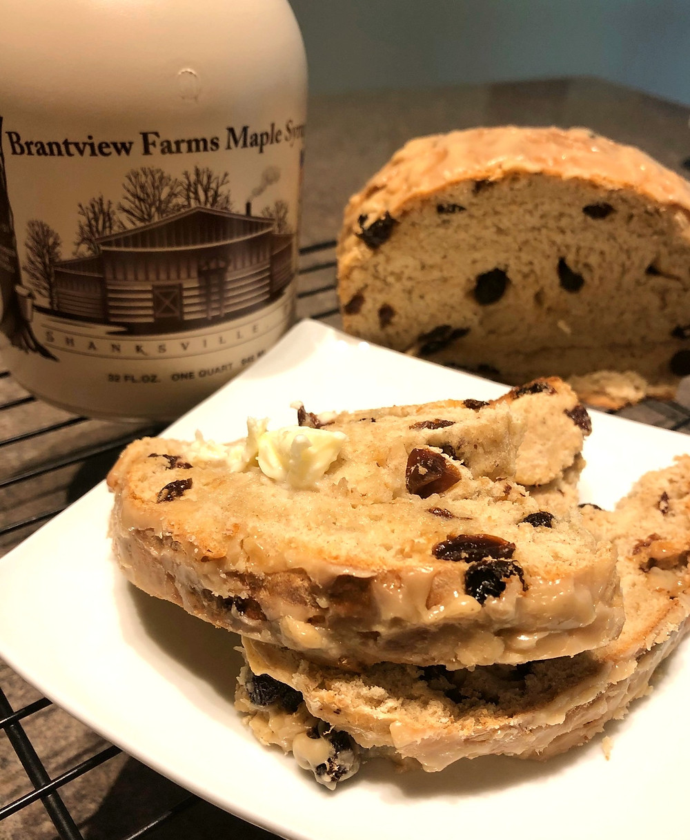 Two slices of bread with raisins sit on a white plate next to a half of a loaf of the same bread. Beside the plate is a brown jug that reads Brantview Farms Maple Syrup