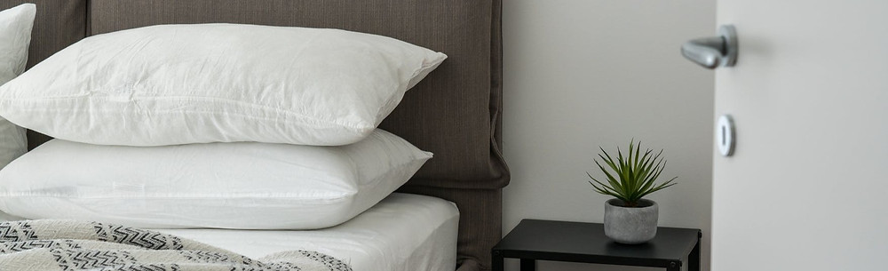 stacked pillows on a bed next to a nightstand in a hotel room