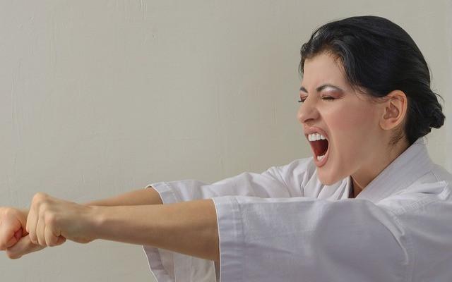 Tummahiuksinen karateka huutaa valkoisessa asussa