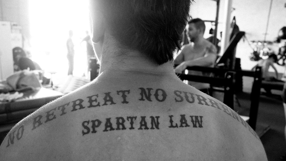 Spartan code tattoo on a boxer's shoulders in a gym