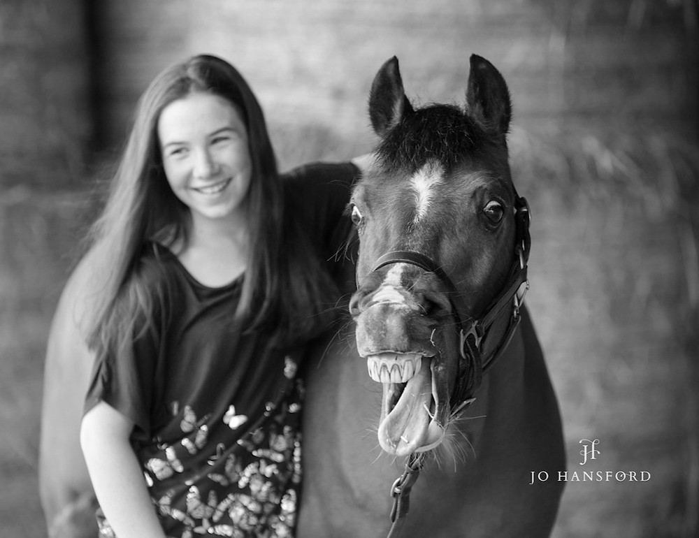 Young girl with her horse pulling a funny face photo by Jo Hansford Photography