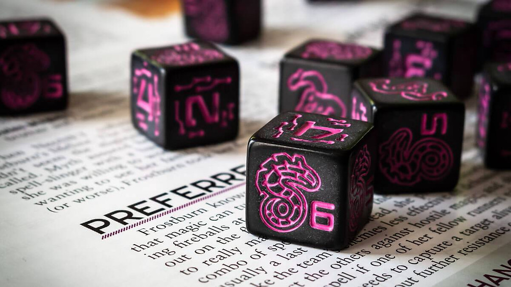 Shadowrun dice on an open book. Dice are black with bright pink engravings: stylized techy numbers and accents throughout the faces and Shadowrun logo with the 6. [Photo credit: Erik Stanfill via Geek Dad]