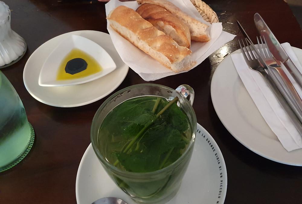 Glastasse mit frischer Minze, Brot, Besteck, Öl und Balsamico in Schale