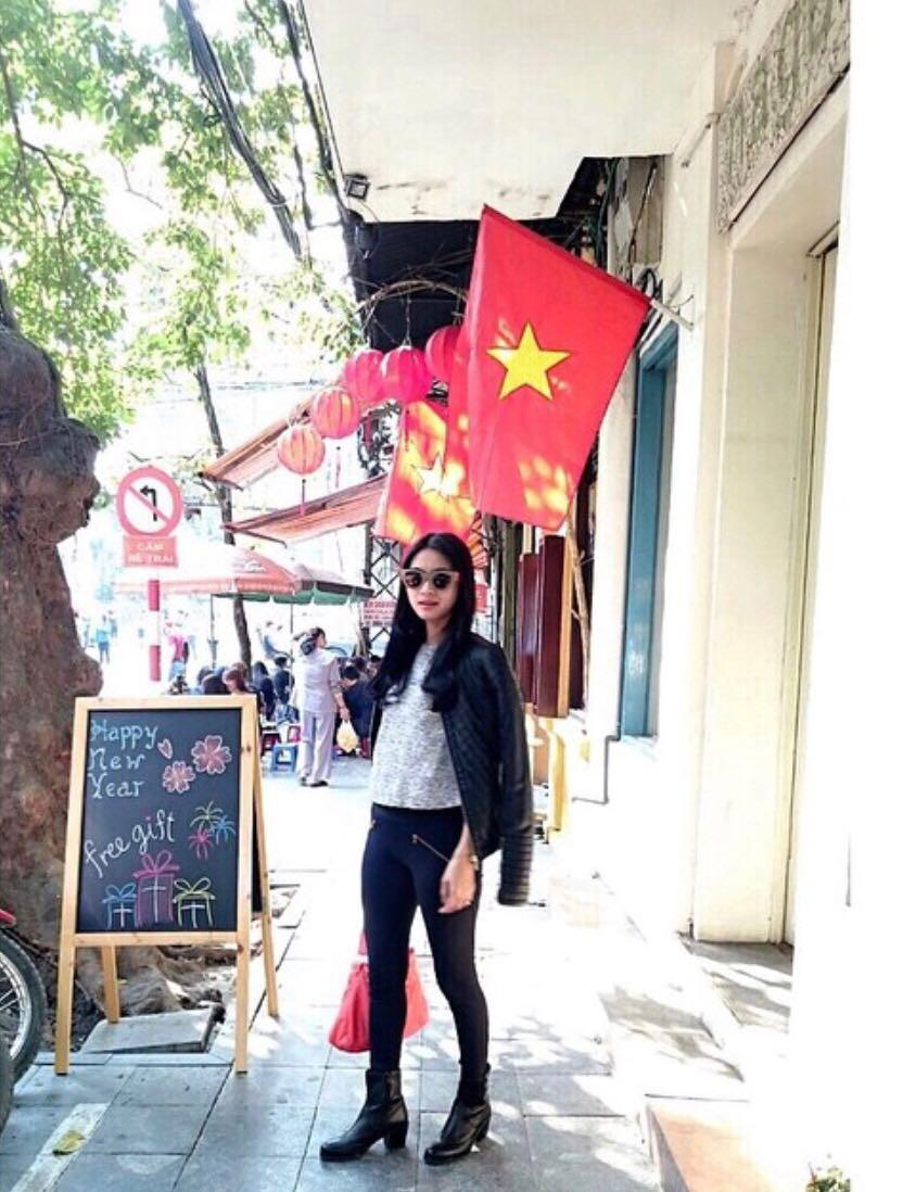 Rini Yulianti di jalan Vietnam dengan latar belakang bendera Vietnam.  #RiniBabyJourney #jurnalRIN