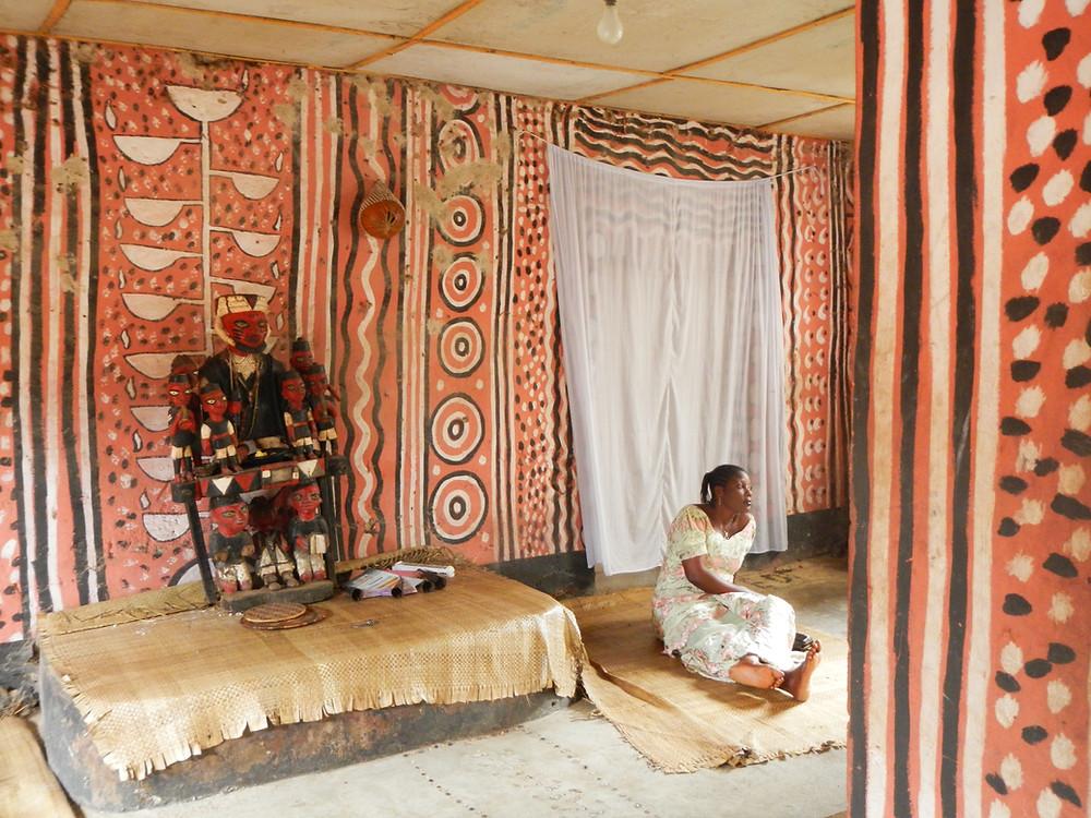 Foto 1: Durante el tiempo de sequía la estatua de Obalúayé se coloca en el Atá (altar) de Oshún. Detrás del mismo, en la pared se puede apreciar la lámpara de 16 puntas (Atupa Olojumerindinlogun) símbolo del pacto de Laaroye con la deidad del río Oshun.  Foto: Nahayeilli Juárez Huet, Palacio de Oshogbo, Nigeria, octubre de 2012