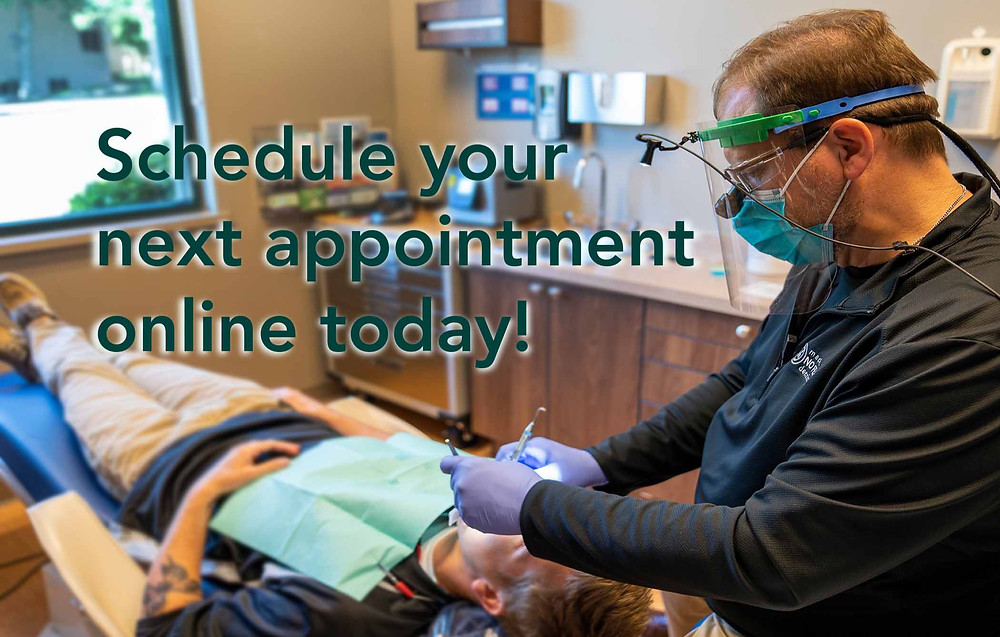 A hygienist at Madison No Fear Dentistry provides treatment for a patient with online appointment schedule graphic