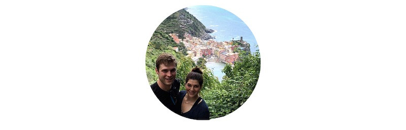 caucasian couple on a hiking trail with a view of cinque terre italy far below in the background