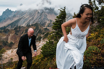 A couple hiking up a mountain in their wedding clothes on their adventurous elopement day near Mount Baker