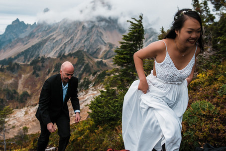 A bride and her groom hike up a mountain near Mount Baker on their wedding day