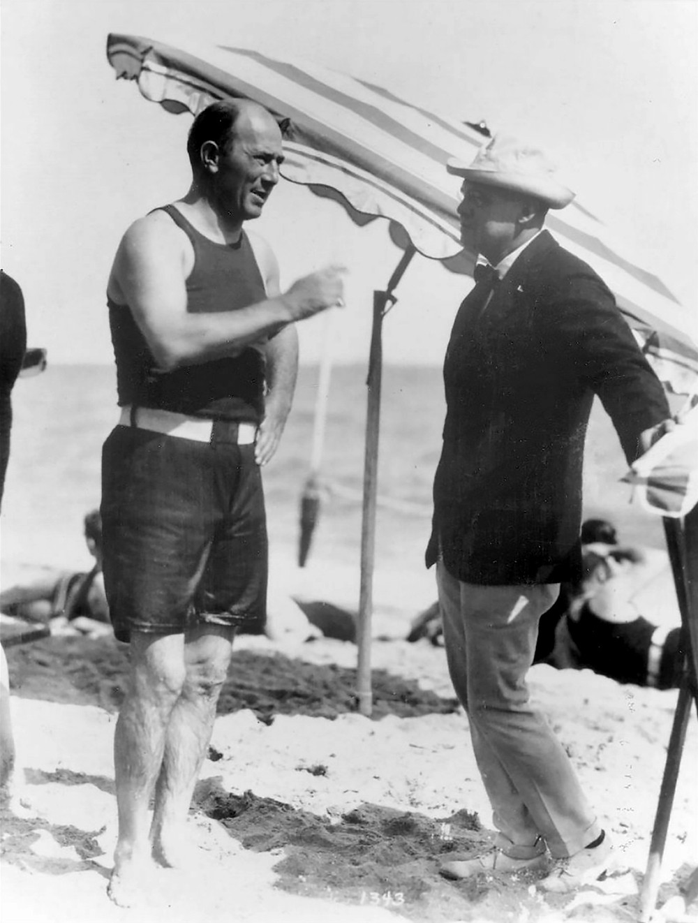 A black and white photograph of Carl Fisher, still dripping from a swim and dressed in black swim top and trunks with a white belt, talks with a photographer.