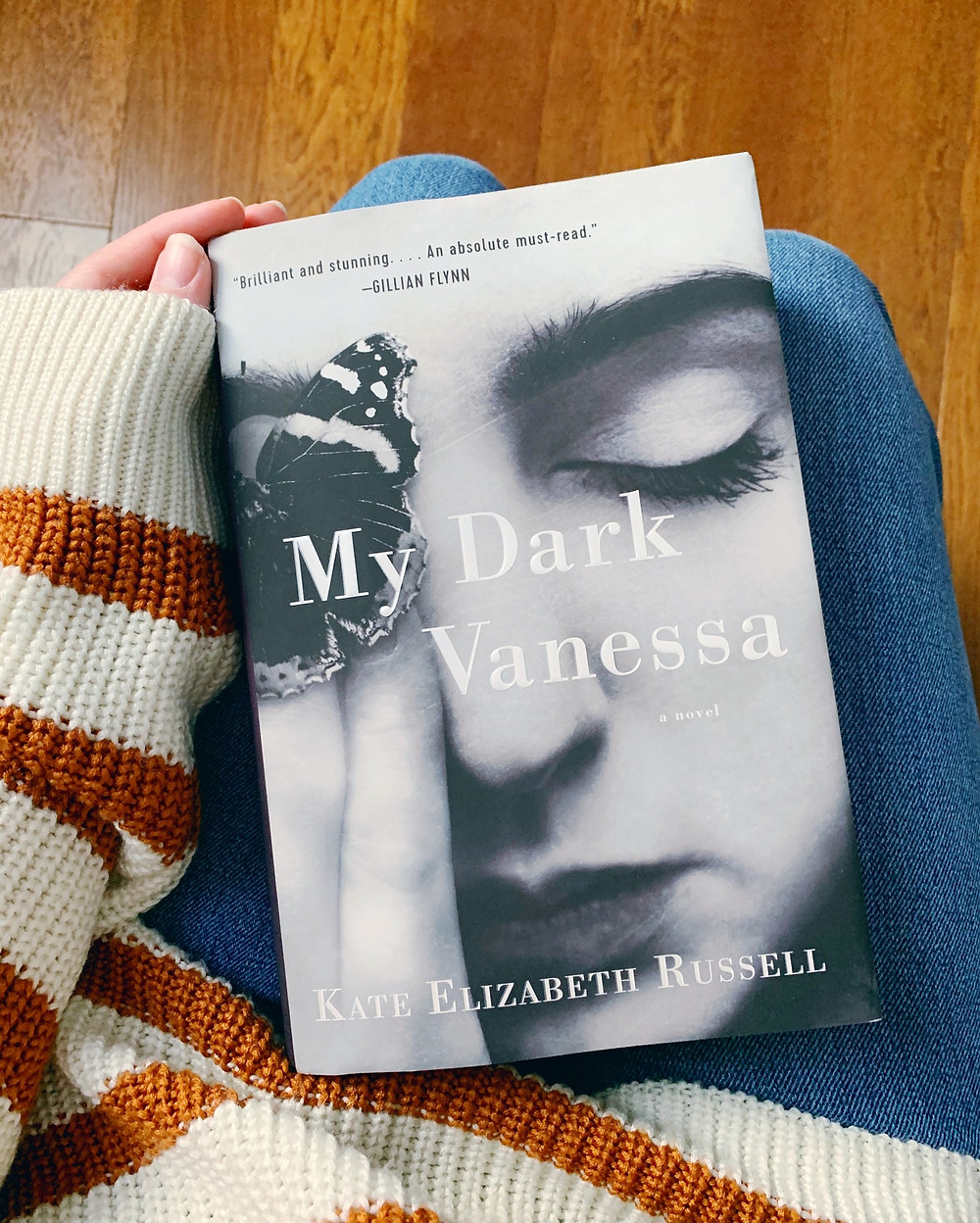 The book My Dark Vanessa sits on a lap wearing jeans, with a striped sweater'd arm holding the top corner