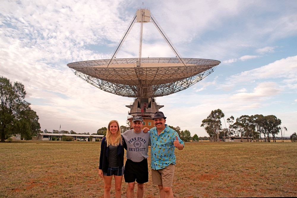 """The author (center) poses with Carolina Camilo and Wilson da Silva in front of the 64-meter antenna of the Parkes Observatory, often simply called """"The Dish,"""" near the town of Parkes, New South Wales."""