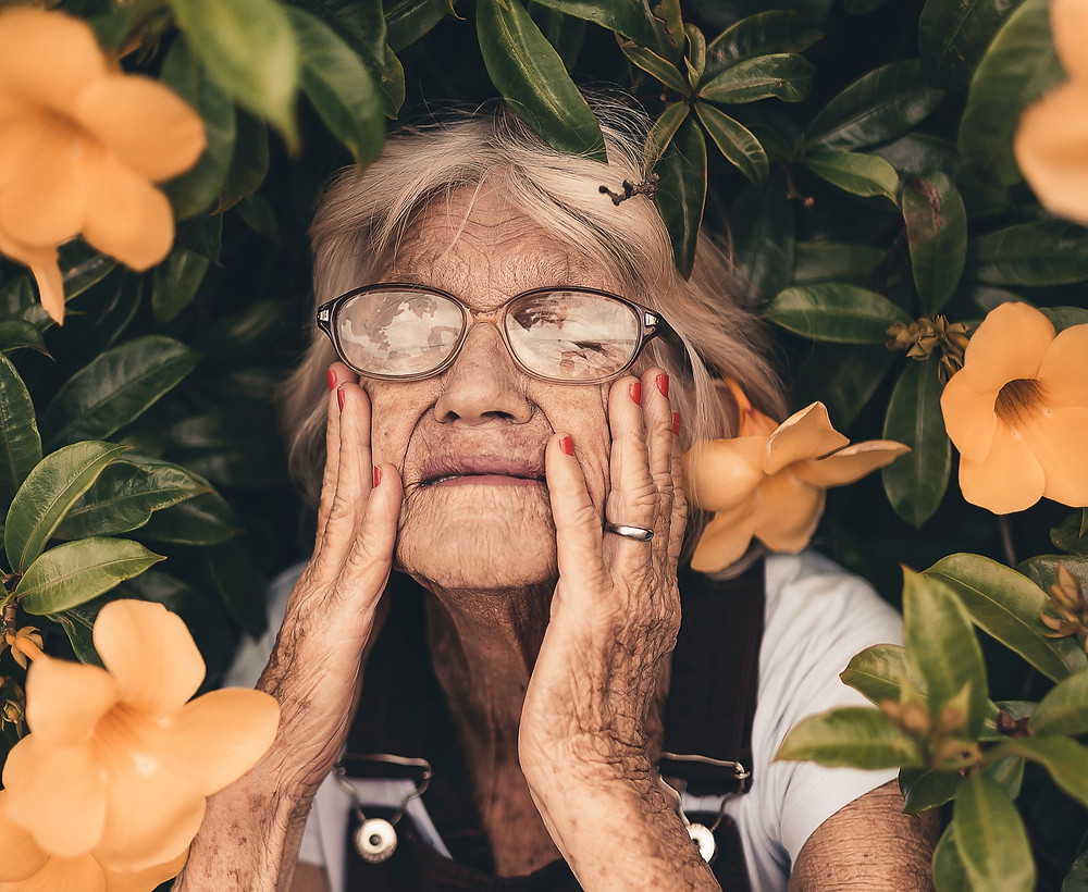 Elderly woman wearing glasses with eyes closed, touching her face, surrounded by green leaves and orange flowers, Photo by Edu Carvalho from Pexels