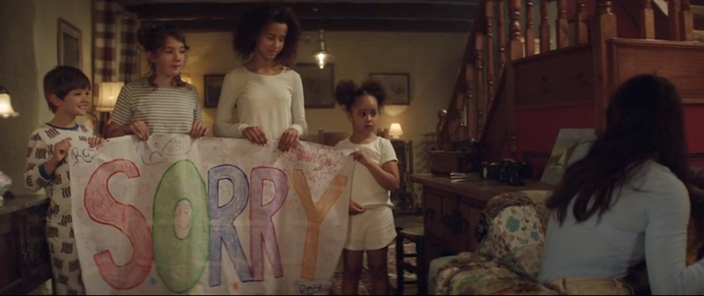 In a cottage interior four children hold a colourful hand made banner reading 'Sorry'