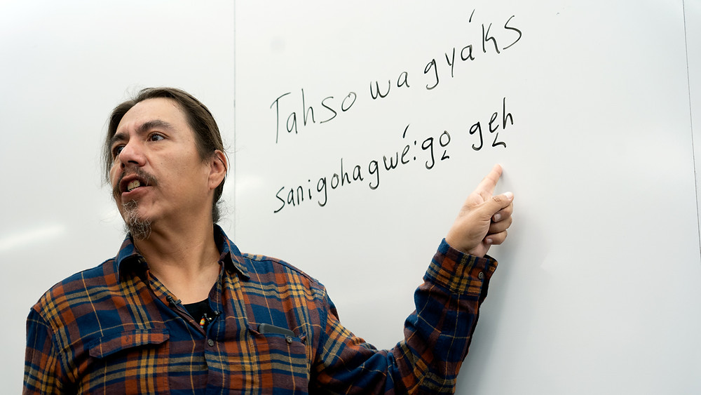 Stephen Henhawk points to Cayuga phrases on a whiteboard