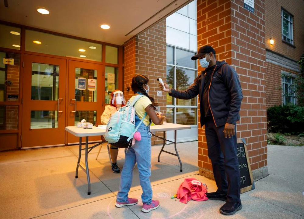 Chequeo de temperatura para el programa de YMCA antes de la clase en la Escuela Pública Elizabeth B. Phin en Pickering, Ontario