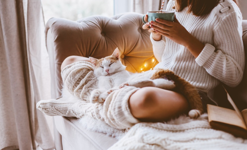 Girl-having-tea-on-cosy-couch-with-cat-and-romantic-lights
