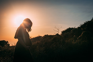 pregnant women in field with sunlight