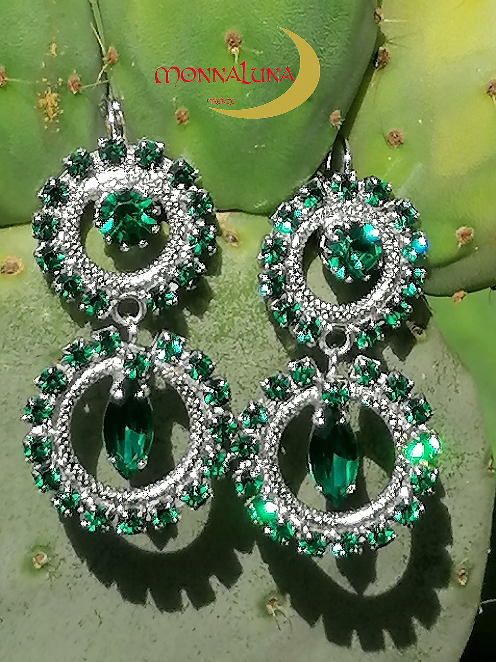 Emerald green crystals surround knurled circle elements in white gold