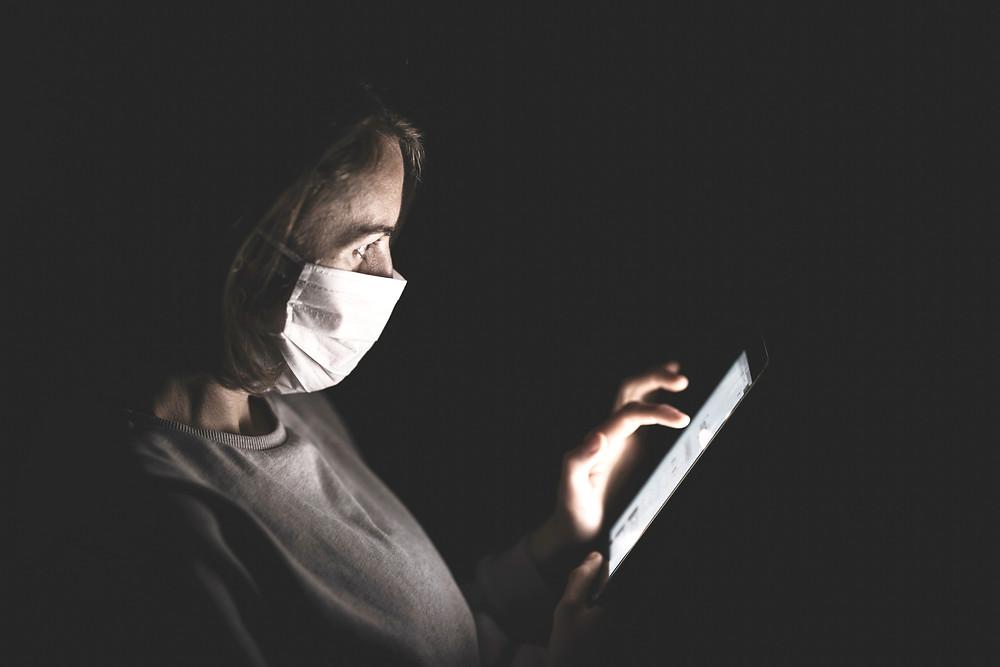 Frau mit Maske und Smartphone