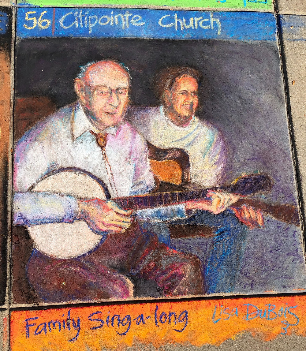 A family singalong, in pastel on sidewalk, depicting a grandfather playing the banjo and his grandson playing guitar.