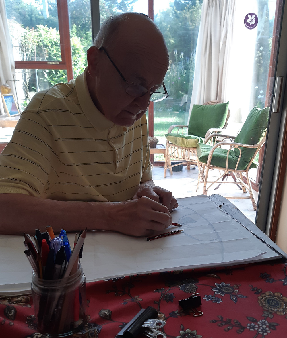 Peter at a table with the design of the painting upside down, using a soft pencil to cover the back so that he can transfer it onto the painting surface.