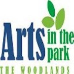 "In blue and green text on a white background the words ""Arts in the park"" with green leaves and the words ""The Woodlands"" below it"