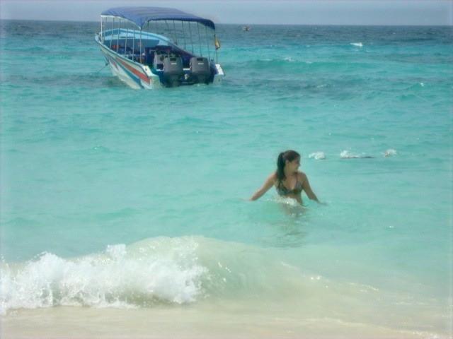 Vista de mujer en el mar celeste con un barco de fondo en  Playa Blanca, Baru, Islas del Rosario, Colombia, Sudamérica