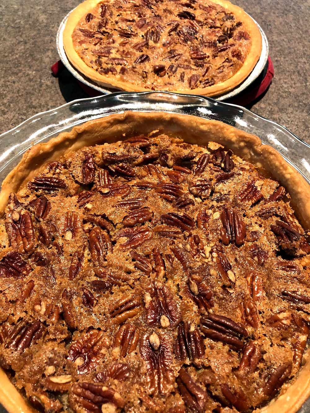Two golden pecan pies sit on a counter, ready to cut and serve.