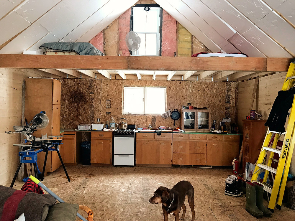 An unfinished kitchen under a loft in a diy cabin