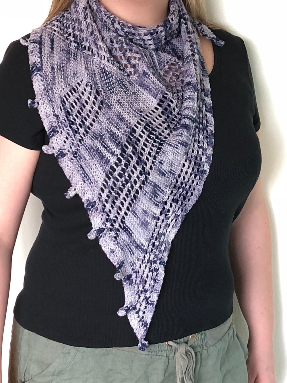A purple hand-knit triangular shawl featuring sections of garter-stitch & mesh with a bobble bind-off.
