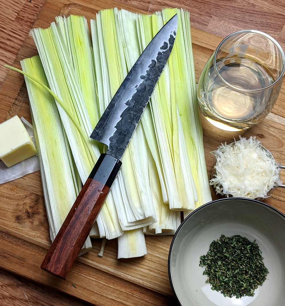 Sliced leeks on display with butter, white wine, thyme, and parmesan
