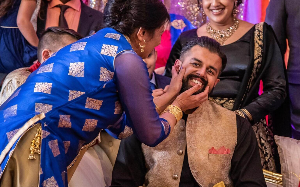 mother in blue saree touching smiling grooms face while other women laugh at him