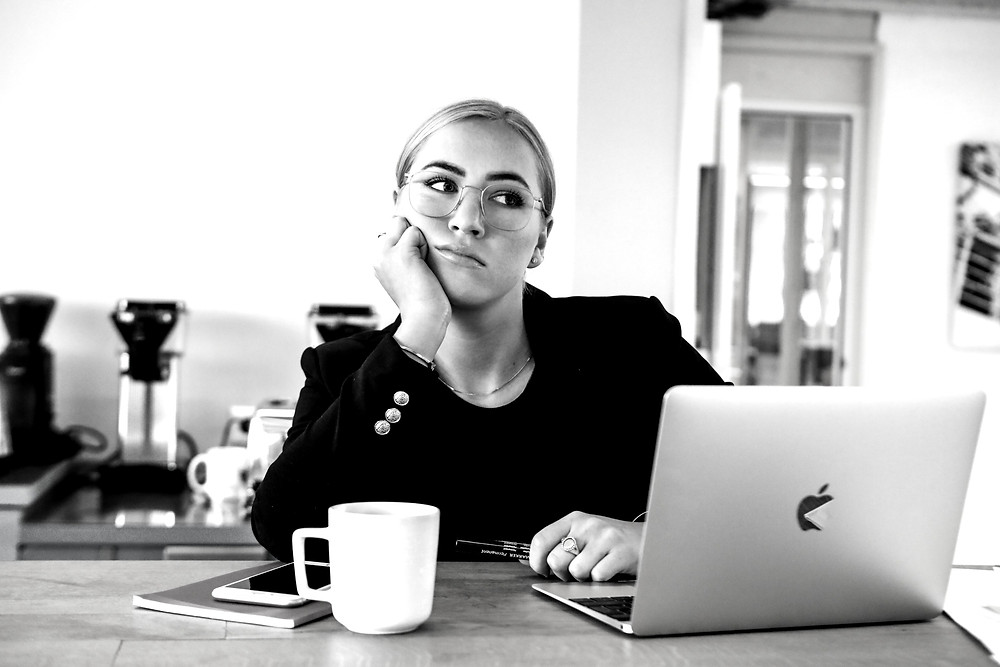 A woman in front of a laptop looking bored