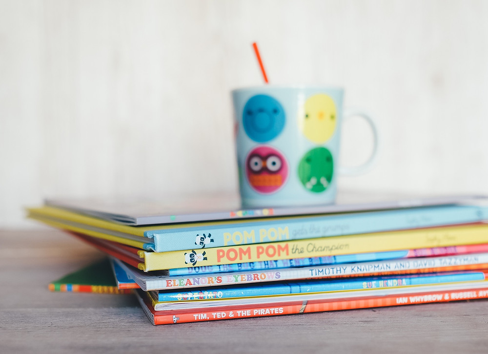 A colorful sippy cup and straw sitting ona pile of easy reader children's books.