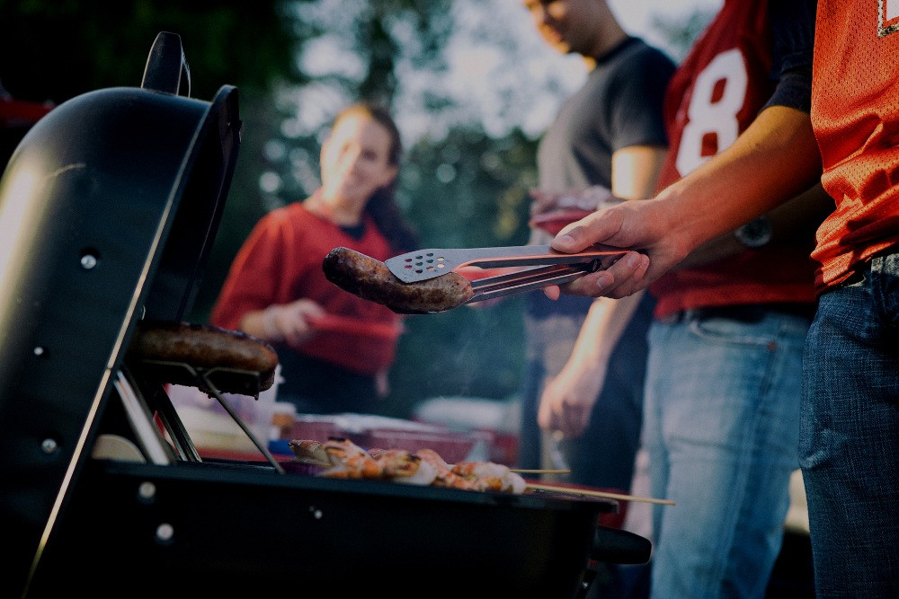 People grilling hot dogs at a tailgate party