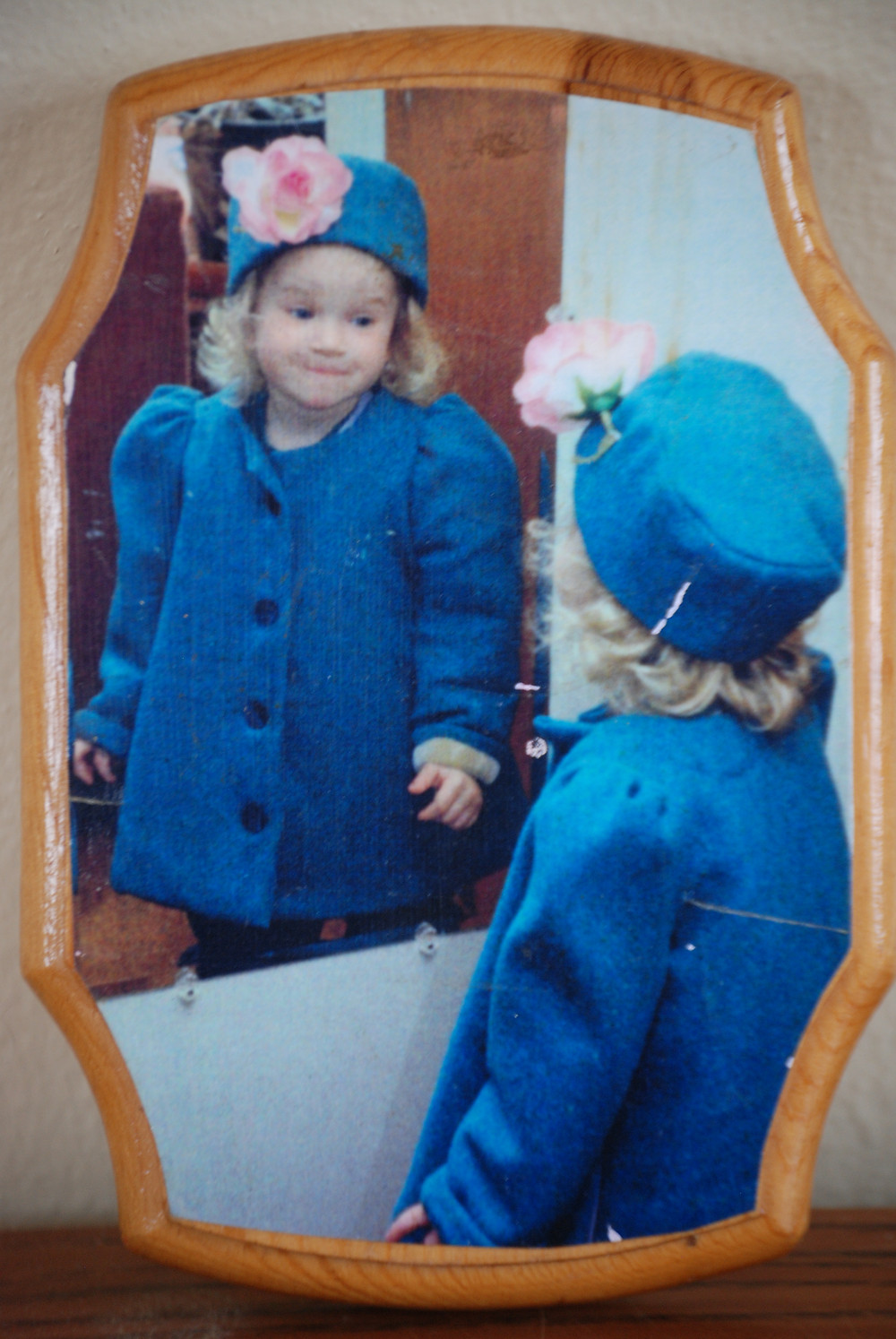 Decoupage  print on wood of a little girl in a fancy coat and matching hat smiling at her reflection in a mirror.