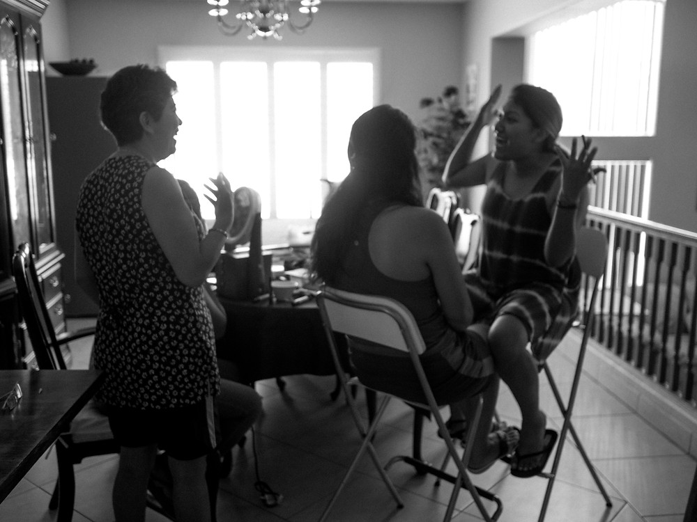 Sisters and mother doing makeup before the wedding