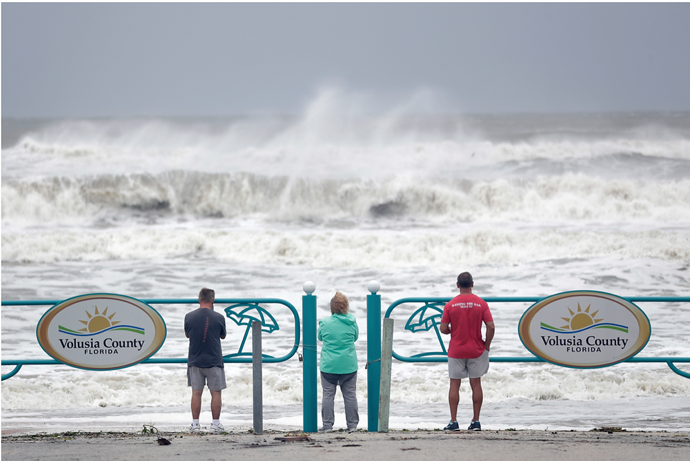 Sightseers watch waves crash on shore as Hurricane Dorian made its way off the Florida coast Wednesday, Sept. 4, 2019, in Ormond Beach, Fla.