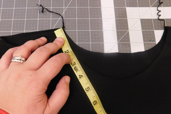 Image of the same black Dream Tee with the finished shoulder seams. A hand holds a yellow tape measure up to the neck opening at the left side to begin measuring.