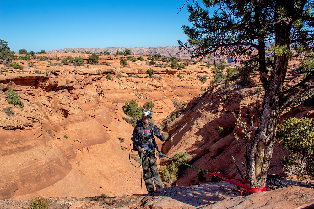 Person rappels into a narrow Utah canyon.