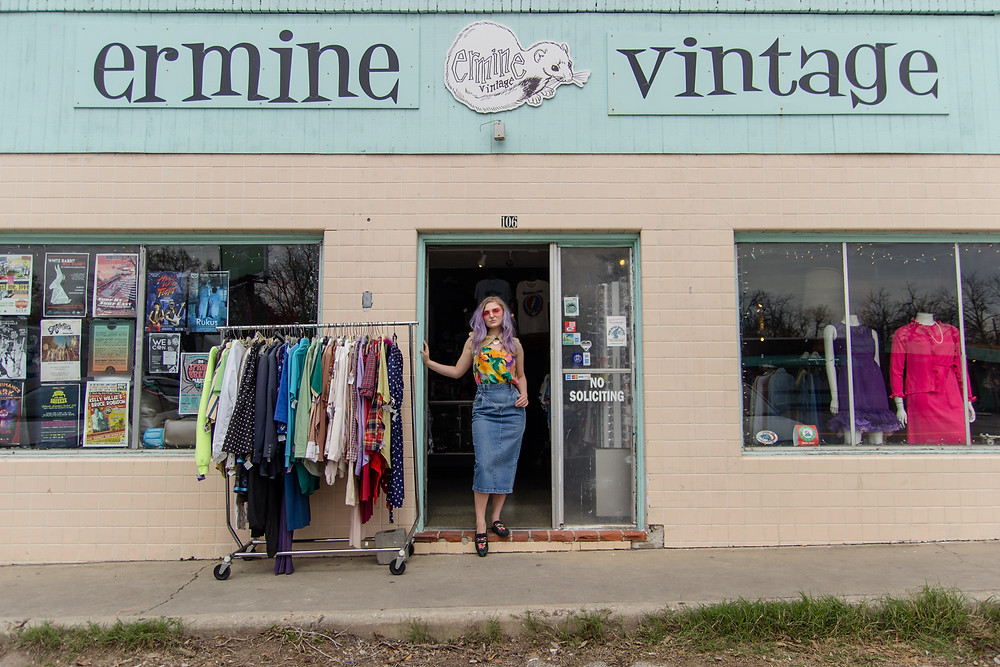 Woman stands in floral blouse and blue jean skirt in front of Ermine Vintage